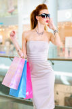 Beautiful fashion woman with shopping bags. Stands at shop royalty free stock photo