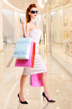 Beautiful fashion woman with shopping bags. Stands at shop royalty free stock image