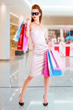 Beautiful fashion woman with shopping bags. Stands at shop stock photo