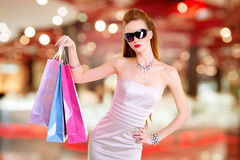Beautiful fashion woman with shopping bags. Stands at shop stock photography