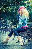 Beautiful fashion woman sitting on a park bench Stock Photography