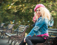 Beautiful fashion woman sitting on a park bench Royalty Free Stock Photography