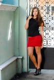 Beautiful fashion woman standing by iron gate Royalty Free Stock Photos