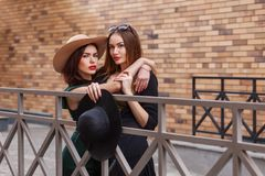 Beautiful fashion women posing. Trendy lifestyle urban portrait on city background. Girls wearing in style clothes and accessories stock images