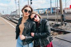 Beautiful fashion women posing. Trendy lifestyle urban portrait on city background.stylish girlfriend in sunglasses at the railway. Beautiful fashion women Royalty Free Stock Photography