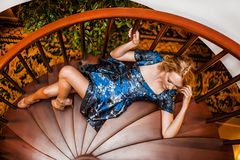 Beautiful fashion wooman posing on steps of staircase Stock Photography