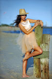 Beautiful and fashion young woman with long legs in luxury dress and hat Royalty Free Stock Photography
