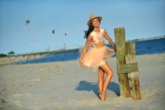 Beautiful and fashion young woman with long legs in luxury dress and hat Royalty Free Stock Photo