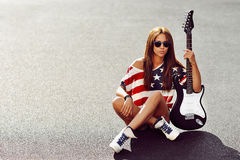 Beautiful and fashion young woman posing with electric guitar Stock Photo