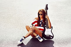 Beautiful and fashion young woman posing with guitar Royalty Free Stock Images