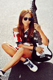 Beautiful and fashion young woman posing with guitar Royalty Free Stock Image