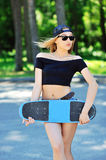 Beautiful and fashion young woman posing with a skateboard Royalty Free Stock Photo