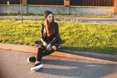 Beautiful fashion young woman sits on the board with a skateboard Royalty Free Stock Images
