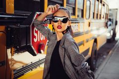 Beautiful fashionable Asian model girl wearing stylish black sunglasses posing outdoors on city street near bus. royalty free stock photography