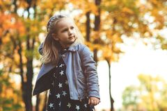 Beautiful fashionable baby girl walking in autumn park. Happy child playing outdoors in autumn. Stylish little girl enjoy sunny da stock image