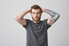 Beautiful fashionable bearded men with colored tattoo on arm and good hairstyle holding hands behind head, looking in. Beautiful fashionable bearded man with royalty free stock photo