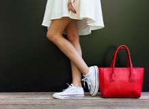 Beautiful fashionable big red handbag standing next to leggy woman in white short dress and white sneakers. Part of body Royalty Free Stock Image