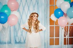 Beautiful fashionable blonde girl in a blouse and skirt posing in interior with colorful balloons.  Royalty Free Stock Photography
