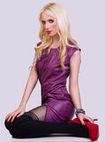 Beautiful fashionable blonde girl in violet dress stock image