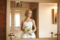 Beautiful and fashionable blonde model girl with wedding hairstyle in trendy dress with bouquet of flowers in her hands royalty free stock images