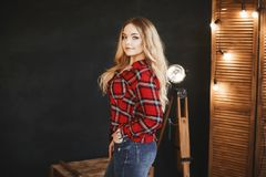 Beautiful and fashionable blonde pluss-size model girl with big breast in red plaid shirt and in a jeans, stands near the wooden c royalty free stock image