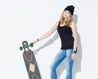 Beautiful fashionable bright young girl in jeans, a black T-shirt and hat posing with a cool longboard in the hands of near a whit Royalty Free Stock Photo