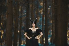 Beautiful and fashionable brunette model girl in the image of Maleficent - fairytale story.  Royalty Free Stock Photos