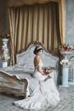 Beautiful and fashionable brunette model girl in stylish wedding dress with naked shoulders sits on the bed with bouquet royalty free stock photo