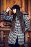 Beautiful fashionable brunette woman with long hair posing near wooden door wearing coat. And a hat Royalty Free Stock Photography