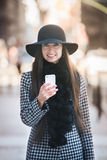 Beautiful fashionable business woman walking on the street and texting on mobile phone Royalty Free Stock Photography