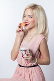 Beautiful fashionable cheerful girl in a pink dress in a retro style with a croissant and a cup of tea on a white background isola Stock Photography