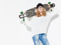 Beautiful fashionable cheerful young girl in a white sweater on the shoulders keeps longboard and posing Stock Photos