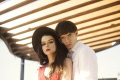 Beautiful fashionable couple on an abstract background. Fashionable hipsters. Girl in a red dress and black big hat. royalty free stock photos