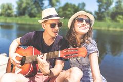 Beautiful fashionable couple with acoustic guitar against lake or river in the background. Summer and relationship concept. Young couple playing acoustic guitar royalty free stock photography
