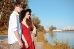 Beautiful fashionable couple on the beach near the river. Fashionable hipsters. Girl in a red dress and black big hat. A men with glasses and a white shirt royalty free stock photo