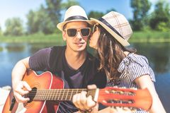 Beautiful fashionable couple in love playing acoustic guitar outdoors. Young musician with acoustic guitar with his girlfriend kissing him against beautiful stock images