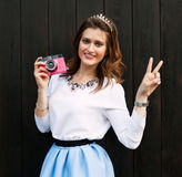 Beautiful fashionable gir with pink vintage camera, a blue short skirt posing near the wooden wall of a warm summer evening. Shows Royalty Free Stock Photo