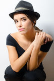 Beautiful fashionable girl in black clothes and black hat agains Stock Photo
