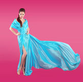 Beautiful fashionable Girl in blowing blue dress. Woman in Flyin Royalty Free Stock Photos