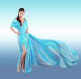 Beautiful fashionable Girl in blowing blue dress. Woman in Flying Gown, Silk Fabric Waving on Wind isolated on studio background. royalty free stock photos
