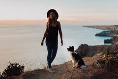 Beautiful fashionable girl on a cliff by the ocean with a dog border collie stock images