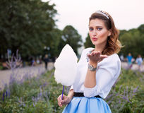 Beautiful fashionable Girl with cotton candy send a kiss in the park in warm summer evening Stock Photos