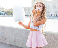 Beautiful fashionable Girl eating cotton candy have fun in warm summer evening on the banks of the river in the city center Royalty Free Stock Images