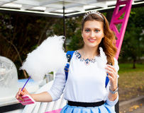 Beautiful fashionable Girl eating cotton candy in the park in warm summer evening Stock Photography