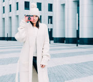 Beautiful fashionable girl in a knit coat on the street European city taking pictures pink vintage camera. Stock Photography