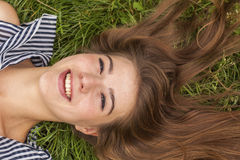 Beautiful fashionable girl lying on the grass. Stock Images
