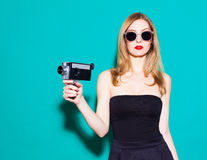 Beautiful fashionable girl posing and holding a vintage movie camera in black dress and sunglasses on the green background in the Stock Photography