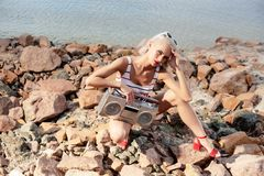 Beautiful fashionable girl posing with retro boombox. On rocky beach stock images