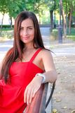 Beautiful fashionable girl sitting on park bench. Brunette posing sexy. Royalty Free Stock Images
