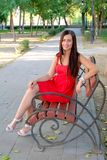 Beautiful fashionable girl sitting on park bench full body Royalty Free Stock Image